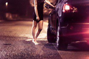 Prostitute standing at a car