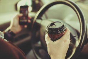 Driver drinking coffee and texting