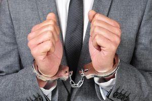 a man wearing a suit, with handcuffs in his wrists