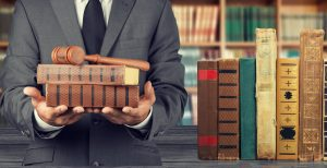 Suited man with law books and gavel