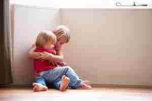 Unhappy children sitting on floor