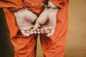 cuffed man in jumpsuit
