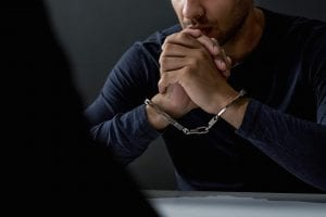 Cuffed man at table